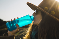 Woman on a hiking trip drinking from water bottle - KKAF00937