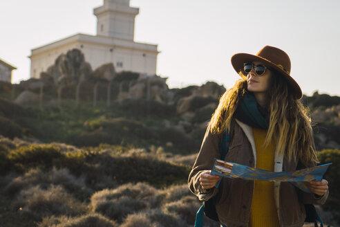 Italy, Sardinia, woman holding map on a hiking trip - KKAF00946