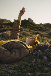 Italy, Sardinia, woman lying in meadow holding up flower - KKAF00952
