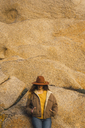 Woman wearing a hat leaning against rock wall - KKAF00967