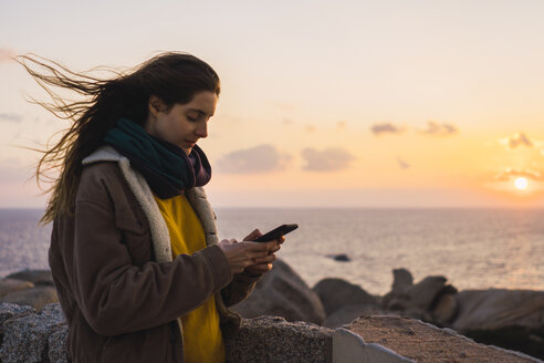 Italy, Sardinia, woman using cell phone at the coast at sunset - KKAF00970