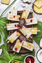 Pina Colada popsicles with candied cherries and pineapple on leaf - RTBF01163
