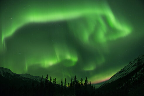 Idyllic view of mountains against aurora borealis at Northern Rocky Mountains Provincial Park - CAVF35717