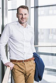 Portrait of smiling businessman standing - UUF13278