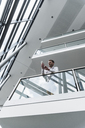 Businessman in office building leaning on railing looking at cell phone - UUF13284