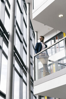 Businessman in office building looking out of window - UUF13287