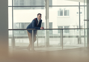 Businessman in office building leaning on railing - UUF13290