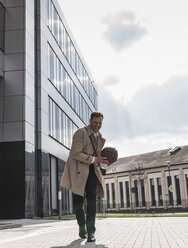 Happy businessman playing basketball outside office building - UUF13296
