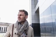 Portrait of businessman outside office building looking away - UUF13299
