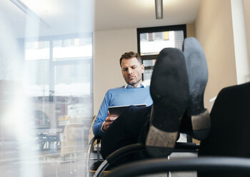 Casual businessman using tablet in office - UUF13305