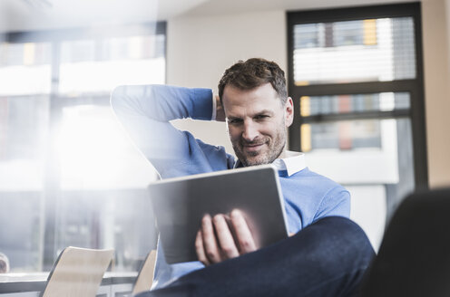 Smiling businessman using tablet in office - UUF13308