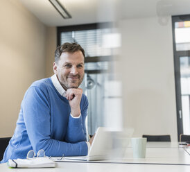 Portrait of smiling businessman with laptop in office - UUF13311