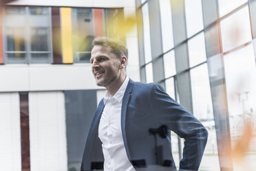 Smiling businessman standing in office building - UUF13317