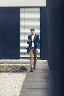 Businessman walking outdoors looking at smartphone - UUF13320