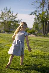 Rear view of girl walking on field at park - CAVF35845