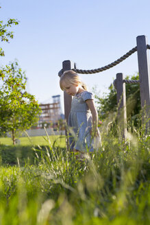 Girl looking down while walking on field at park - CAVF35848