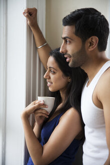Couple looking away while standing by window at home - CAVF35944