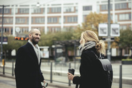 Mid adult businessman talking with businesswoman at tram station - MASF02269