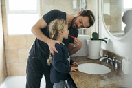 Mid adult father brushing daughter's teeth at sink in bathroom - MASF02293