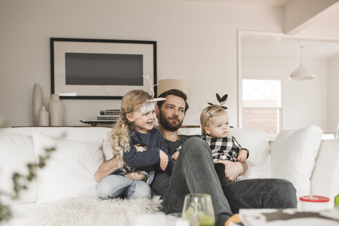 Mid adult man with daughters sitting on sofa in living room at home - MASF02296