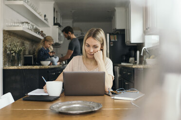 Mid adult woman using laptop at table with family in kitchen at home - MASF02302