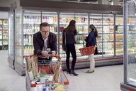 Mature man using mobile phone while leaning on shopping cart against women buying juices at refrigerated section in supe - MASF02305
