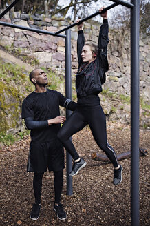 Mid adult man assisting woman exercising on monkey bars in forest - MASF02311