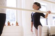 Cute ballerina looking at male teacher in studio - CAVF36122