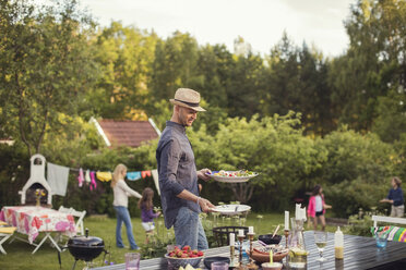 Man carrying plates by dining table in back yard during garden party - MASF02312