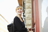 Low angle view of smiling businesswoman unlocking office door with key - MASF02333