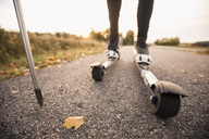 Low section of man roller skiing on country road - MASF02336