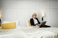 Mature businesswoman sitting on bed using laptop against wall at hotel room - MASF02348