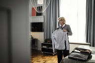 Mature businesswoman holding shirt against window at hotel room - MASF02351