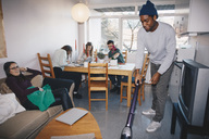 Man cleaning floor while friends sitting in college dorm room - MASF02354