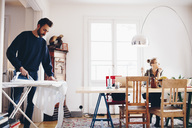 Man ironing while woman looking away in dining room at home - MASF02357