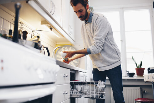 Man cleaning utensils in kitchen at home - MASF02360