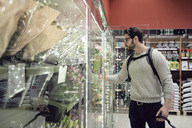 Man standing by flowers on display at supermarket - MASF02363