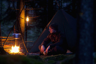 Man relaxing while cooking food on campfire in forest at night - MASF02366