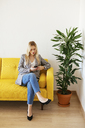 Businesswoman sitting on yellow couch, using smartphone - EBSF02336