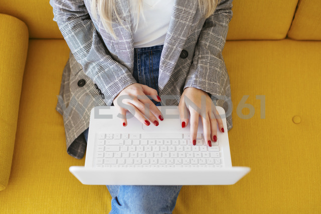 Businesswoman sitting on yellow couch, using laptop - EBSF02342 - Bonninstudio/Westend61