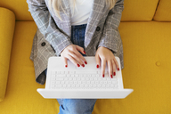 Businesswoman sitting on yellow couch, using laptop - EBSF02342