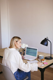 Blond businesswoman sitting at desk, working - EBSF02357