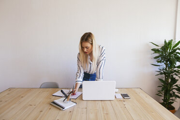 Young businesswoman standing at desk, using laptop - EBSF02381