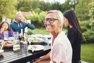 Happy woman sitting with friends and family at dining table in back yard during garden party - MASF02372