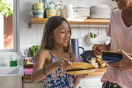 Happy girl holding plates with mother in kitchen at home - MASF02378