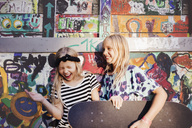 Happy friends with skateboards enjoying against multi colored wall - MASF02381