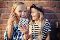 Happy girls listening music through smart phone while sitting against brick wall - MASF02384