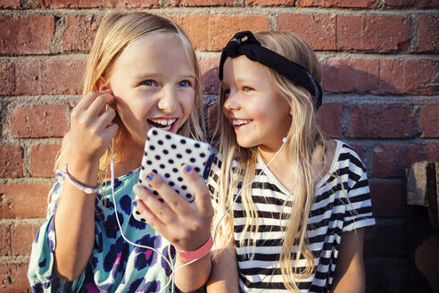 Happy girls listening music through smart phone while sitting against brick wall - MASF02384