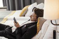 High angle view of businessman using mobile phone listening to music while lying on bed at hotel room - MASF02411