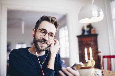 Happy man listening to music in mobile phone at home - MASF02414